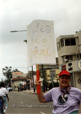"""P024.509m.r.t 1989 San Diego Pride Parade: Sally Hopkins holding a sign that reads, """"Dyke out of control"""""""
