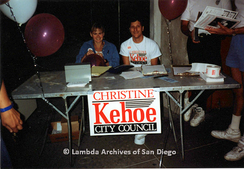P151.038m.r.t A man and a woman sitting at a campaign table
