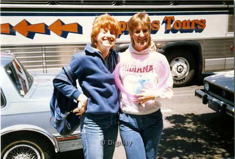 P104.194m.r.t Dignity San Diego: Two women in front of a tour bus, with the one on the left holding a pink heart shaped balloon.