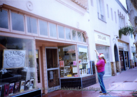 P167.028m.r.t Paradigm Women's Bookstore: Woman cleaning wall and windows of store front