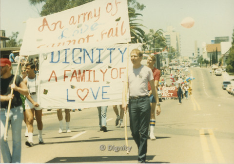 "P104.131m.r.t Dignity L.A. at San Diego Pride Parade: Men holding sign saying ""An army of Love cannot fail"" in front of men carrying a sign saying ""Dignity A Family of L<3ve"""