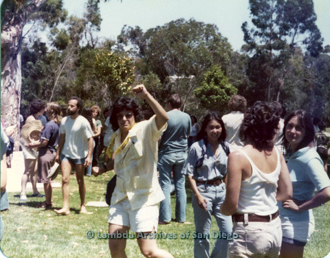 P109.003m.r.t San Diego Pride Festival 1976: Woman pumping fist in air at a gathering in a Balboa Park.