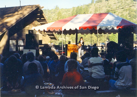 P024.221m.r.t  Woman playing guitar on Day stage as audience looks on