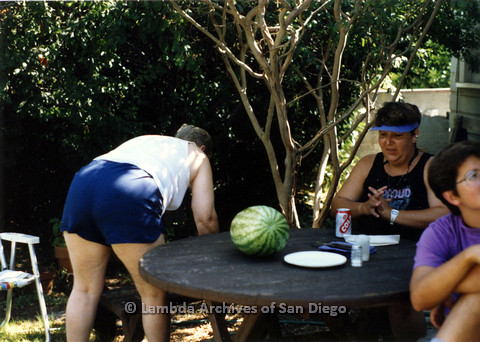 P024.319m.r.t Commonwealth: Three women around a table with a watermelon on it. Sally Hopkins is bent over looking at ground.