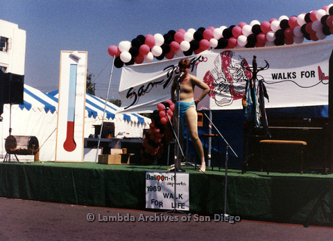 P024.209m.r.t  Judith McConnell wearing a blue bikini bottom and a flesh colored suit on stage