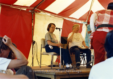 P024.254m.r.t Phyllis Lyons (left) and Del Martin (right) seated at the Day stage speaking in to microphones.