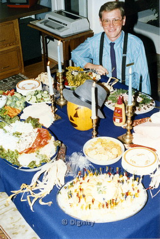 P104.086m.r.t Dignity San Diego: Man posing besides a table of food, decorated with a drawn on pumpkin and maize
