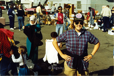 "P104.004m.r.t Dignity church and MCC yard sale: Smitty smiling in front of yard sale wearing hat "" Dignity Yard Sale Co-Chair: Ask me…I know everything"""