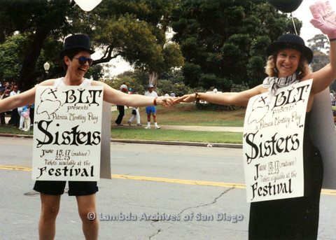 "P024.468m.r.t 1990 San Diego Pride Parade: (From left to right) Kithy Gately and Ellie Rapp hold hands wearing sandwhich boards advertising ""Sisters"", a Beautiful Lesbian Thespians play."