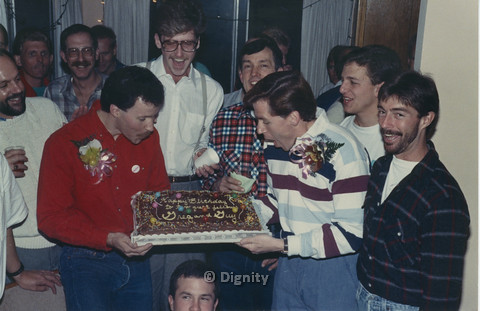 "P104.076m.r.t Dignity San Diego: Group of men surrounding two men holding cake with words : ""Happy Birthdayto the great fellows Greg and Guy"""