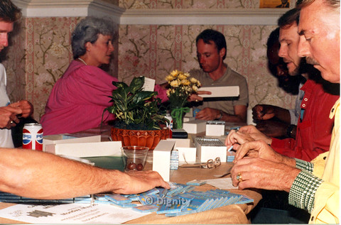 "P104.043m.r.t Dignity San Diego: Bruce Neveu (in red polo) and others sitting around table, handling small boxes with words ""PLAY SAFE"""