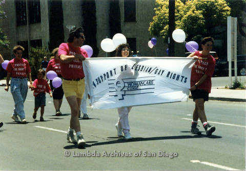 P024.425m.r.t 1990 San Diego Pride parade: People marching in parade holding Woman Care Clinic banner