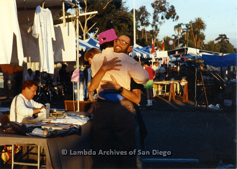 P024.522m.r.t 1990 San Diego Pride: Judith McConnell in pink hat hugging unknown man in the midst of the booths