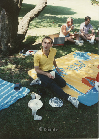"P104.060m.r.t Dignity Picnic 4th of July: Man in yellow polo sitting on blanket with words ""LIFE'S A BEACH"""