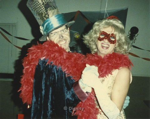 P104.099m.r.t Dignity San Diego:  Bruce Neveu and a person in a dress, red boa, and red domino mask