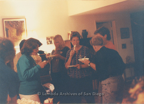 P024.371m.r.t A group of women converses while eating cake. Sally Hopkins in black and jeans is facing away