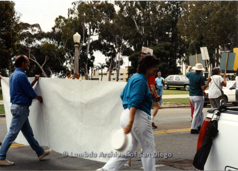 P024.415m.r.t 1990 San Diego Pride parade: Mel Merril and unidentified people marching in parade holding the San Diego Democratic Club banner