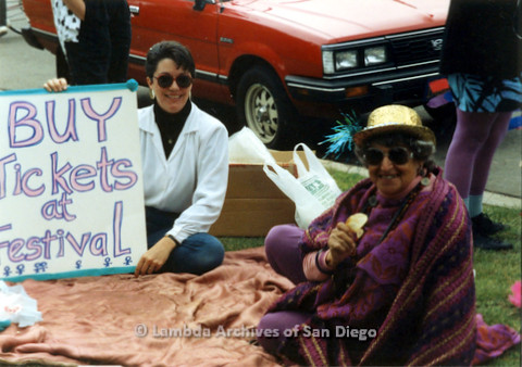 "P024.434m.r.t 1990 San Diego Pride Parade: Muriel Fisher (right) and another woman sitting on a blanket on the grass. Woman on left is holding a sign that reads ""Buy tickets at the festival"""