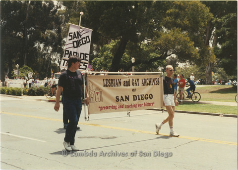 "P024.390m.r.t 1989 San Diego Pride Parade: A Generation Of Pride: Two people holding a banner that say ""Lesbian and Gay Archives of San Diego; Peserving and teaching our History"""