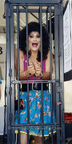 1995 - San Diego LGBT Pride Festival: - Drag Queen Caged at the Leather Realm Booth Area.