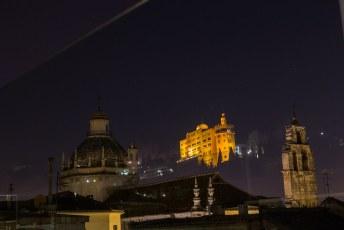 's Avonds reflecteerden de sterren en het hotel Alhambra Palace in het glas van het balkon terwijl de kerk aan de overkant erdoorheen zichtbaar is.
