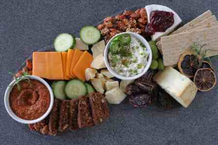 cheese board with dips, crackers and nuts