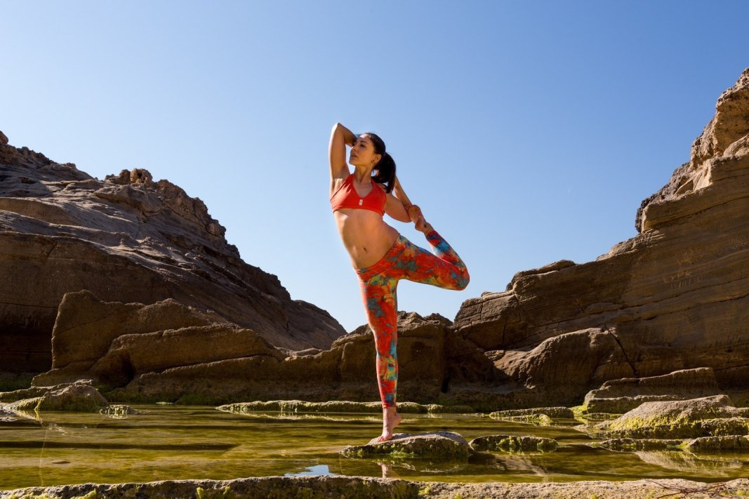 a woman does yoga next to some tide pools