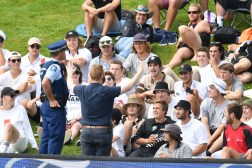 The police try to calm rowdy students during day two of the 1st International cricket Test match between New Zealand and South Africa at the University Oval in Dunedin on March 9, 2017. / AFP PHOTO / Marty MELVILLE