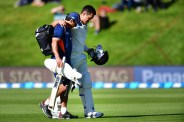 New Zealand's Ross Taylor (Back) is helped from the field injured during day two of the 1st International cricket Test match between New Zealand and South Africa at the University Oval in Dunedin on March 9, 2017. / AFP PHOTO / Marty MELVILLE