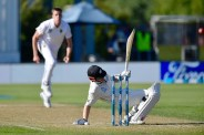 New Zealand's captain Kane Williamson (R) bats from the ground watched by South Africa's Morne Morkel during day two of the 1st International cricket Test match between New Zealand and South Africa at the University Oval in Dunedin on March 9, 2017. / AFP PHOTO / Marty MELVILLE
