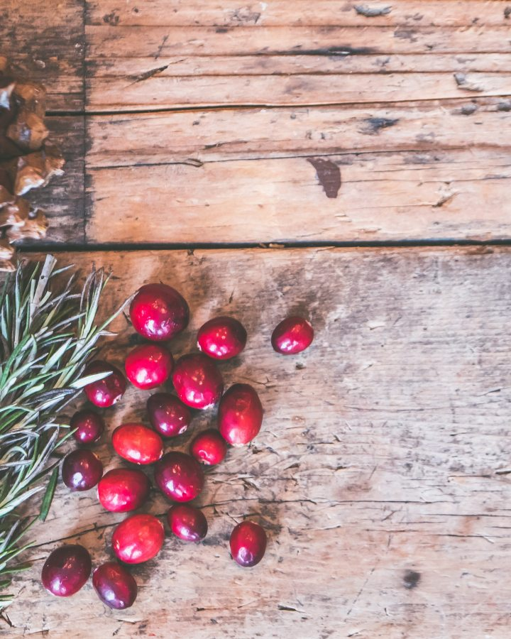 wooden textured surface with pines leaves and berries