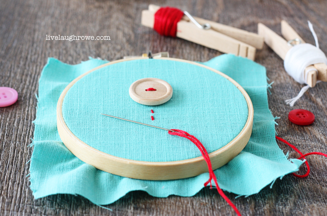 Sewing on buttons as flowers to fabric for Valentine's Day Embroidery Hoop Art
