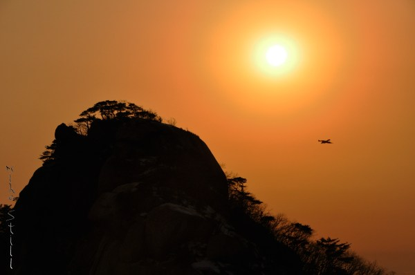Crow flying into a setting Bukhansan sun