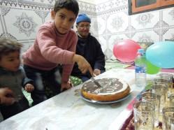 Adil cutting his cake.
