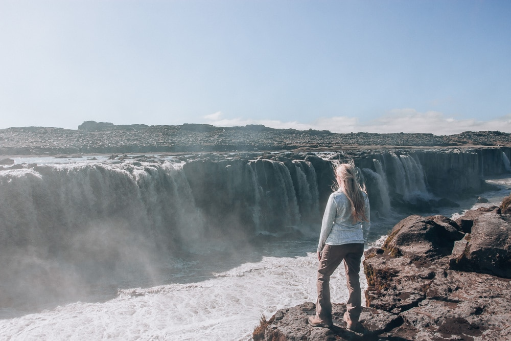 Standing on edge of cliff looking at Selfoss Waterfall in Iceland. Find the top 5 waterfalls in Iceland that you don't want to miss on a Ring Road road trip.