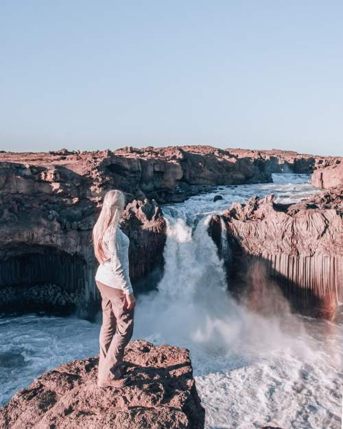 A woman looks at Aldeyjarfoss waterfall in Iceland. Get a full guide to Iceland's Ring Road with this Iceland road trip itinerary.