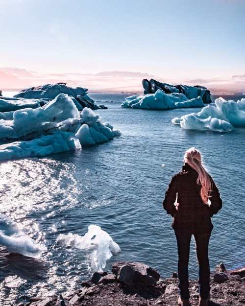 Standing at the edge of Jokulsarlon Glacier Lagoon in Iceland in summer near sunset. Get all the best Iceland photo locations and Iceland travel tips in our ultimate 6 day Iceland itinerary.