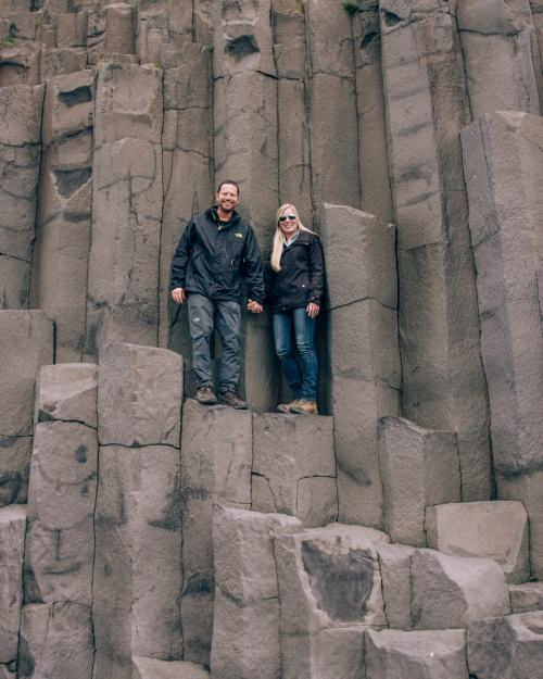 Couple standing on the Basalt columns at Reynisfajara Beach near Vik in Iceland. Get our full Iceland travel guide including the best photo spots in Iceland in our 6 day Iceland itinerary.