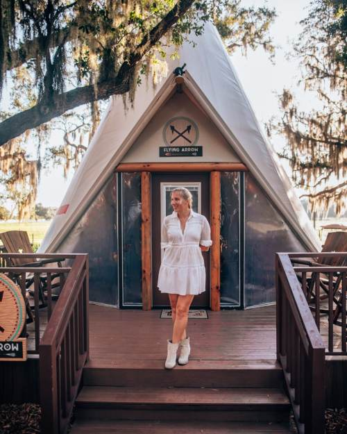 Woman in front of teepee in western inspired outfit with white dress and boots.