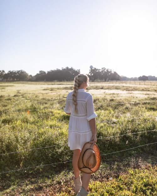 Woman in white dress from Aggie Swimwear, cowboy hat, and boots looking out over pastures while glamping in Florida at Westgate River Ranch.