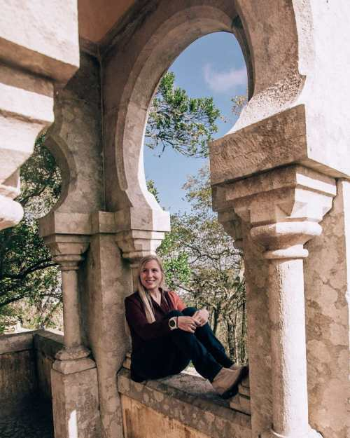 Woman sitting in a window at Pena Palace in Sintra