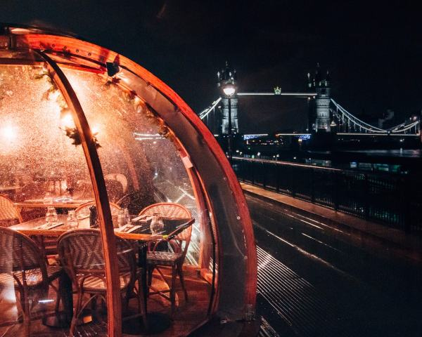 Coppa Club igloos at night with the Tower Bridge in the distance. Find all the best Christmas in London locations here (plus a free map!)