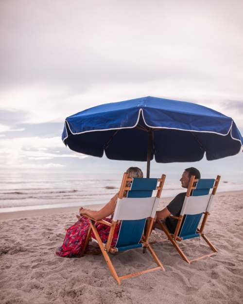 Relaxing with my husband under a beach umbrella in lounge chairs on Westgate Cocoa Beach Resort's beach with concierge services. Find a full review of this resort and the services it offers for a perfect beach vacation here.