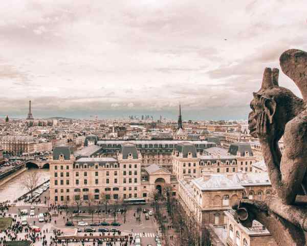 A gargoyle at the top of Notre Dame with the Eiffel Tower in the background. Find all the best photo spots in Paris in winter with a guide to New Year's in Paris here.