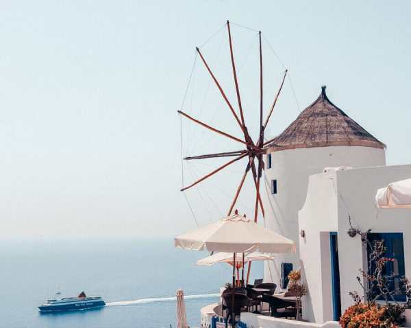 A ferry going past a windmill in Santorini, Greece