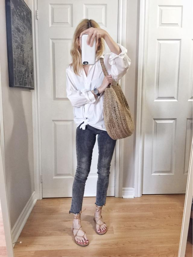 I am wearing an oversized white blousingrey skinny jeans, a woven circle purse, and Madewell sandals
