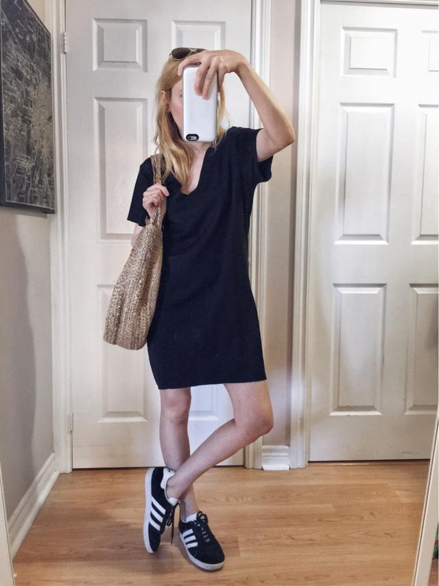 I am wearing a black t-shirt dress. Adidas Gazelle, and a woven circle bag