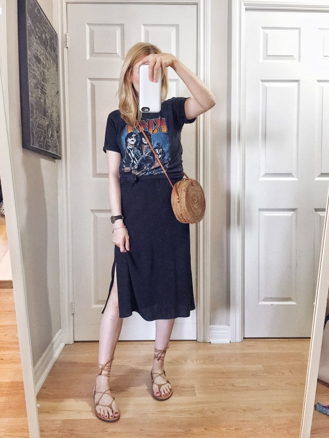 I am wearing a black slip dress with a knotted band tee over top, Madewell Boardwalk sandals, and a small circle purse