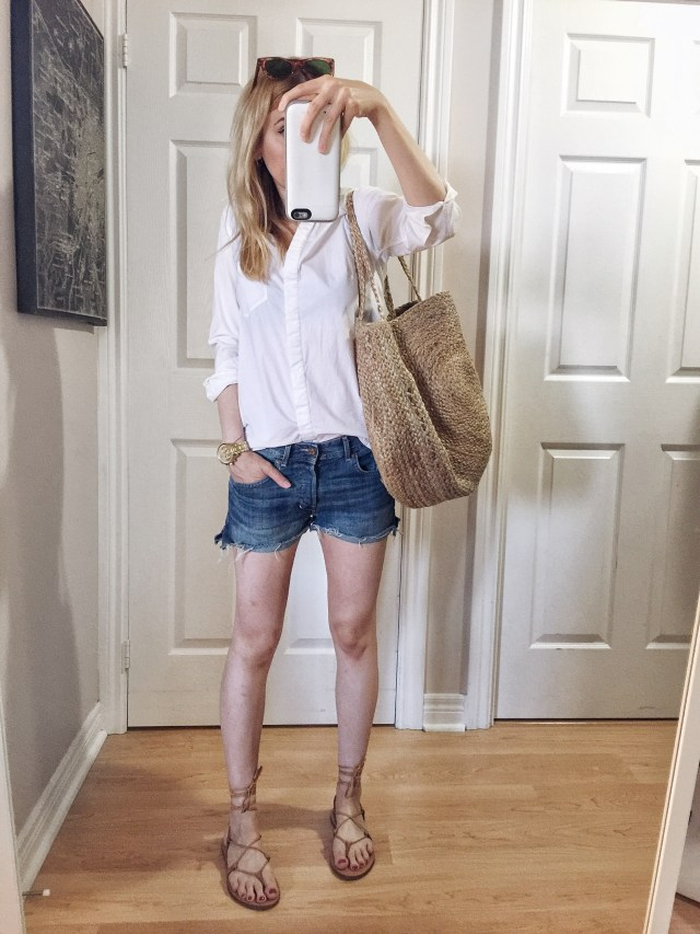 I am wearing denim shorts, a classic white bouton up, Madewell Boardwalk sandals, and a large woven purse.
