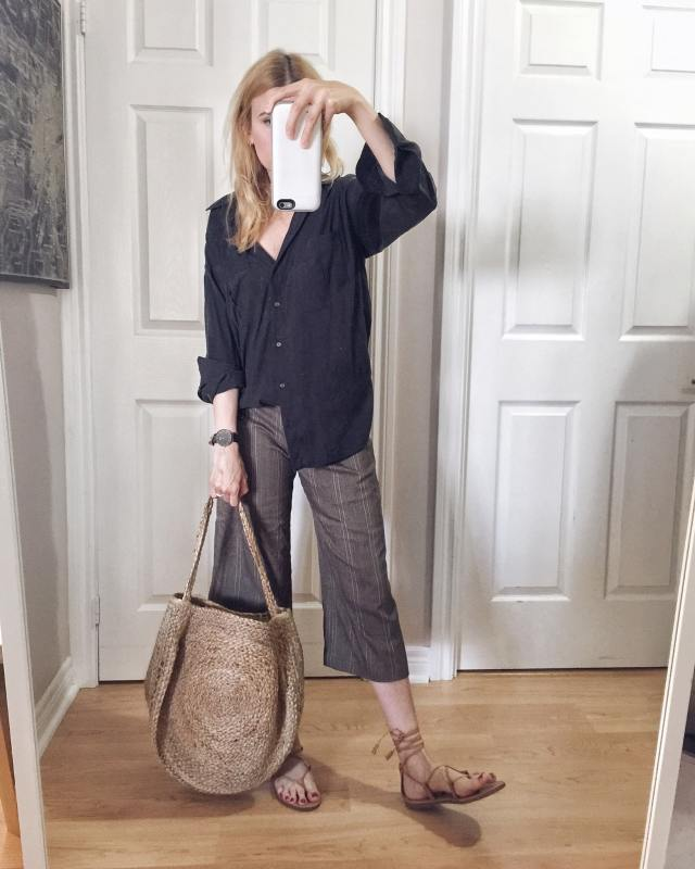 I am wearing a black silk blouse, culottes, a large woven circle purse, and Madewell Boardwalk sandals